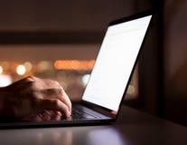 Kvinna` s räcker genom att använda datorbärbara datorn med den tomma skärmen på skrivbordet in arkivbild