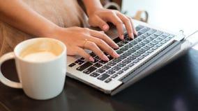 Kvinna` s räcker maskinskrivning på datoren Arkivbilder