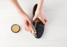 Kvinna` s räcker rena män läderskor för ` s på vit Fotografering för Bildbyråer