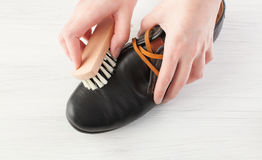Kvinna` s räcker rena män läderskor för ` s på vit Royaltyfria Bilder