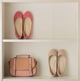 Kvinna` s skor den balettskor och påsen i den vita garderoben Royaltyfri Foto