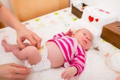 Kvinna som ändrar baby'sens blöja arkivfoton
