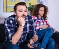 Kvinna som är borrad hållande ögonen på tv med pojkvännen arkivbild