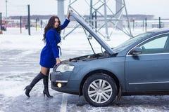 Kvinna som är hållande på till huven av hennes bil Arkivbilder