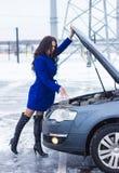 Kvinna som är hållande på till huven av hennes bil och tillfälligt att se motorn Royaltyfria Bilder