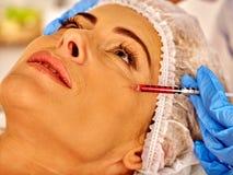 Kvinna som är medelålders i brunnsortsalong med kosmetologen Arkivfoto