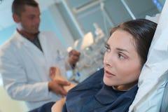 Kvinna som är nervös av injektion arkivfoto
