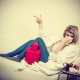 Kvinna som är sjuk ha influensa som ligger på soffan Arkivfoto