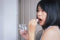 Kvinna som är sjuk med preventivpilleren som sätter i hennes mun, kvinnlig som tar mediciner och ett exponeringsglas av vatten arkivbilder
