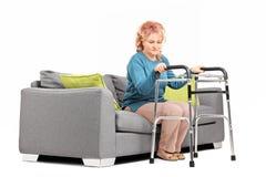 Kvinna som är stående upp från en soffa med fotgängaren arkivfoton