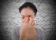 Kvinna som är stressad mot den vita tegelstenväggen med grungesamkopieringen Arkivfoton