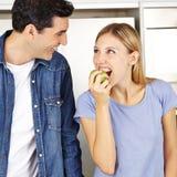 Kvinna som äter äpplet nära man i kök Royaltyfria Bilder
