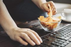Kvinna som äter chiper från bunken på hennes arbetsplats Arkivfoto