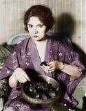 Kvinna som äter choklader ut ur en bunke (alla visade personer inte är längre uppehälle, och inget gods finns Leverantörgarantier arkivfoto