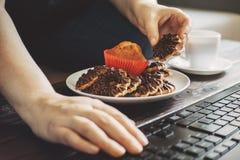 Kvinna som äter chokladkakor på arbetsplatsen Royaltyfria Foton