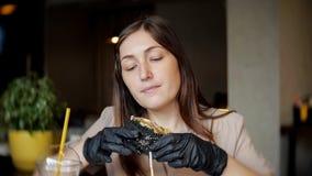 Kvinna som äter den fega hamburgaren för snabbmat på restaurangen arkivbild