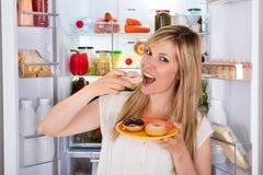 Kvinna som äter den söta munken nära kylskåpet Royaltyfria Bilder