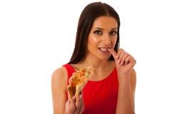 Kvinna som äter det smakliga stycket av pizza Sjukligt snabbmatmål Fotografering för Bildbyråer