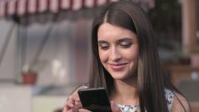Kvinna som äter efterrätten och använder hennes telefon på det friakafét lager videofilmer