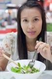 Kvinna som äter en nudel Arkivbild
