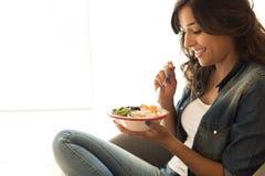 Kvinna som äter en strikt vegetarianbunke royaltyfri foto