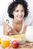 Kvinna som äter en sund frukost med sädesslag på morgonen på säng Fotografering för Bildbyråer