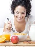 Kvinna som äter en sund frukost med sädesslag på morgonen på säng Arkivbild