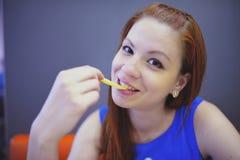 Kvinna som äter fransmansmåfiskar inom kafét arkivbilder