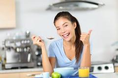 Kvinna som äter frukostsädesslag som dricker fruktsaft Arkivfoto