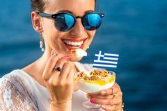 Kvinna som äter grekisk yoghurt royaltyfri bild