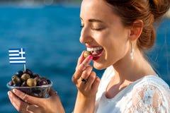 Kvinna som äter grekiska oliv arkivfoto