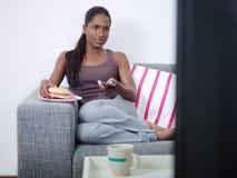 Kvinna som äter hamburgaren och håller ögonen på tv:n arkivfoto