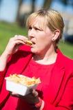 Kvinna som äter hamburgaren och pommes frites royaltyfria foton
