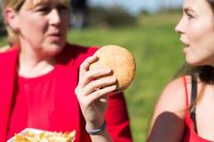 Kvinna som äter hamburgaren och pommes frites royaltyfri fotografi