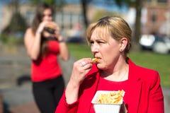 Kvinna som äter hamburgaren och pommes frites fotografering för bildbyråer