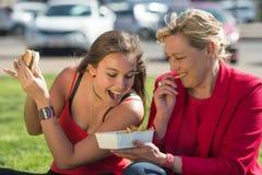 Kvinna som äter hamburgaren och pommes frites arkivfoton