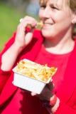 Kvinna som äter hamburgaren och pommes frites arkivbild