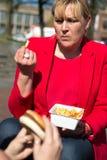 Kvinna som äter hamburgaren och pommes frites arkivbilder