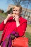 Kvinna som äter hamburgaren och pommes frites royaltyfri foto