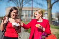 Kvinna som äter hamburgaren och pommes frites arkivfoto