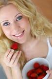Kvinna som äter jordgubbar royaltyfria bilder