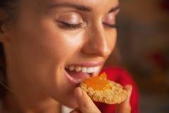 Kvinna som äter kakan med orange driftstopp Royaltyfri Bild