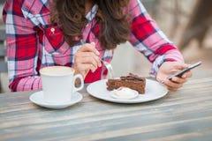Kvinna som äter kakan på kafét Arkivfoton