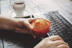 Kvinna som äter muffin på arbetsplatsen Royaltyfria Bilder