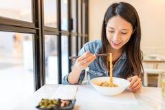 Kvinna som äter nudlar i kinesisk restaurang royaltyfria foton