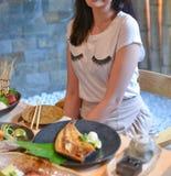 Kvinna som äter och tycker om japanskt mål arkivfoto