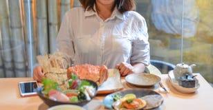 Kvinna som äter och tycker om japanskt mål arkivfoton
