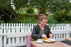 Kvinna som äter på ett utvändigt kafé royaltyfria foton