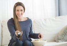 Kvinna som äter popcorn, medan hålla ögonen på TV Arkivfoton