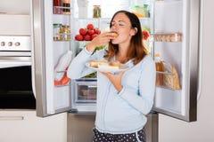 Kvinna som äter söt mat nära kylskåpet Arkivbilder